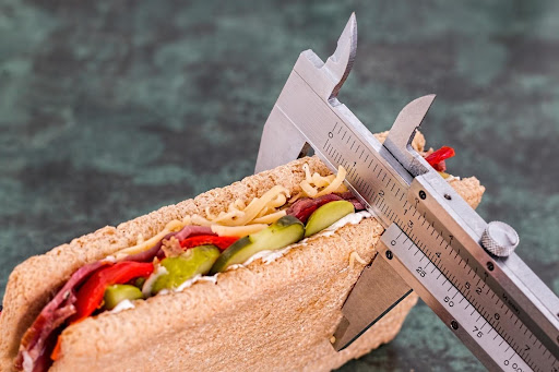 Using a vernier caliper to measure the width of a sandwich against a grey background